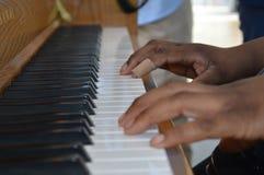 关闭弹钢琴的手 免版税库存图片