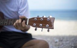 关闭弹经典吉他的英俊的人坐海滩在假期 免版税库存图片