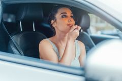 关闭得到她的嘴唇的美丽的妇女被绘,当坐在汽车时 免版税库存照片