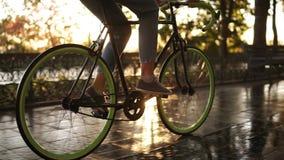 关闭循环一辆自行车在早晨公园或大道的女性脚英尺长度  乘坐a的年轻女人的侧视图 股票录像
