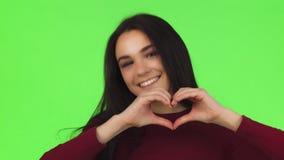 关闭微笑一名愉快的美丽的妇女显示心脏标志 股票视频
