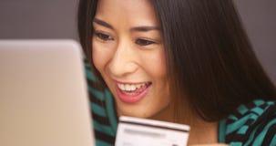 关闭微笑与信用卡的日本妇女 库存图片