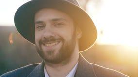 关闭微笑和调查在街道的照相机的有胡子的年轻行家商人画象户外 免版税库存图片