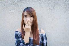 关闭微笑和闪光对灰色混凝土墙的愉快的年轻亚裔妇女画象  葡萄酒口气过滤器颜色样式 免版税库存图片