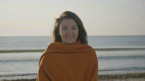 关闭微笑在海滩的一个beautful女孩的画象,当风吹她的头发-时 股票视频