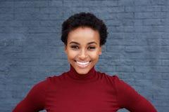 关闭微笑对灰色墙壁的美丽的年轻黑人妇女 库存图片