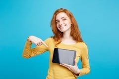 关闭微笑画象年轻美丽的可爱的redhair的女孩显示在黑色的数字式片剂屏幕 蓝色柔和的淡色彩 图库摄影