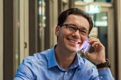 关闭微笑的商人使用现代巧妙的电话,工作在他的办公室和拿着手机的年轻愉快的人 库存图片