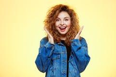 关闭微笑的惊奇的美丽的深色的卷曲女孩画象偶然街道牛仔裤夹克的在黄色 免版税图库摄影