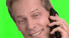 关闭微笑的成熟人面孔谈话在电话 股票录像