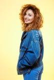 关闭微笑的美丽的深色的卷曲女孩画象偶然街道牛仔裤夹克的在黄色背景 库存图片