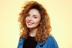 关闭微笑的美丽的深色的卷曲女孩画象偶然街道牛仔裤夹克的在黄色背景 图库摄影