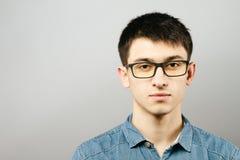 关闭微笑的年轻商人佩带的镜片,看照相机反对与拷贝空间的灰色墙壁背景 库存图片