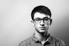 关闭微笑的年轻商人佩带的镜片,看照相机反对与拷贝空间的灰色墙壁背景 免版税图库摄影