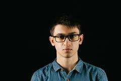 关闭微笑的年轻商人佩带的镜片,看照相机反对与拷贝空间的灰色墙壁背景 库存照片
