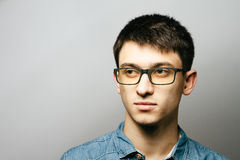 关闭微笑的年轻商人佩带的镜片,看照相机反对与拷贝空间的灰色墙壁背景 免版税库存图片