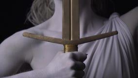关闭忒弥斯的手有一张金黄剑和面孔的与眼罩,4k 影视素材