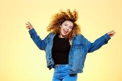 关闭快乐的笑的美丽的深色的卷曲女孩画象跳过黄色的偶然街道牛仔裤夹克的 免版税图库摄影