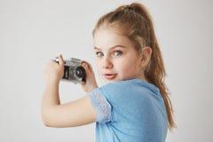 关闭快乐的逗人喜爱的女孩画象有金发和蓝眼睛的,看在与感兴趣的表示的照相机 免版税库存照片