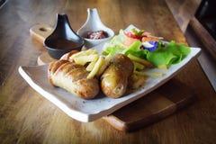 关闭快餐热狗和炸薯条在木桌上 免版税图库摄影