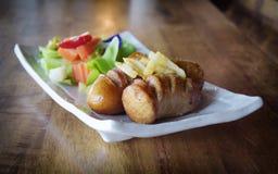 关闭快餐热狗和炸薯条在木桌上 免版税库存图片