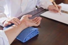 关闭患者的手,当Takes Pulse医生时 免版税库存照片