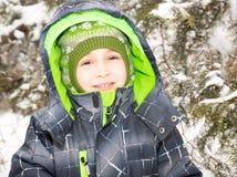关闭愉快地咧嘴在照相机的可爱的愉快的小男孩画象在一晴朗的冬天` s天 库存照片