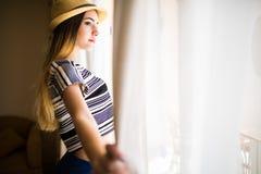 关闭愉快妇女佩带偶然和帽子开窗口帷幕 库存照片
