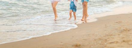 关闭愉快的三口之家-美丽的妻子、获得父亲和的女儿乐趣走在海滩在日落 家庭旅行的concep 图库摄影