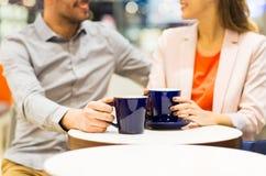 关闭愉快的在购物中心的夫妇饮用的咖啡 库存照片