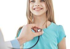 关闭愉快的女孩和医生身体检查的 免版税库存照片