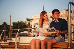 关闭愉快的年轻夫妇坐木甲板在por 免版税图库摄影