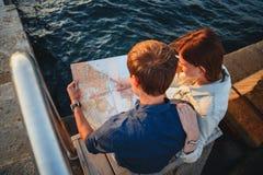 关闭愉快的年轻夫妇坐木甲板在por 免版税库存图片