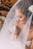 关闭愉快的时髦的白肤金发的新娘画象豪华白色礼服的有花束的在面纱下 免版税库存图片