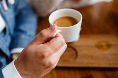 关闭成功的事务的胳膊开与他的客户的一个业务会议在咖啡馆 衣服的人喝咖啡 平均观测距离 库存图片