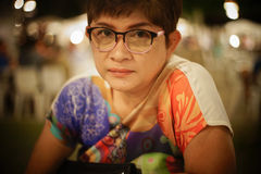关闭成熟亚洲妇女微笑和看照相机画象有被弄脏的背景,选择聚焦,被过滤的图象 图库摄影