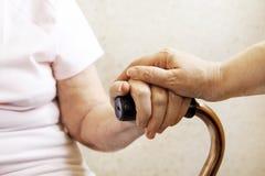 关闭成熟妇女&护士手 给的医疗保健,老人院 祖母父母亲爱  老与年龄有关的疾病 免版税图库摄影