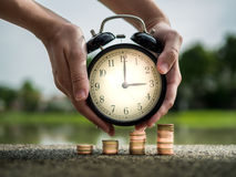 关闭手与堆硬币,货币时间价值的保留时间在企业财务题材的概念 节约金钱的远期 图库摄影