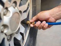 关闭手停放轮胎填满空气f的检查的人汽车 图库摄影