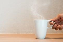 关闭手停滞一杯白色咖啡 免版税库存图片