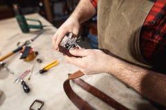 关闭手制革工人进行在桌上的工作与工具 免版税库存照片