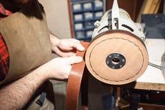 关闭手制革工人进行在桌上的工作与工具 库存图片