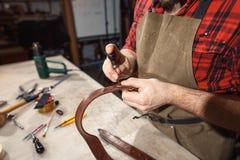 关闭手制革工人进行在桌上的工作与工具 免版税库存图片