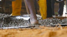 关闭手动地铲起在堆的无法认出的印地安人湿水泥在建筑工地 运作地方的建造者  股票录像