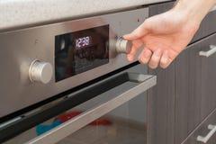 关闭手在烤箱的设置温度控制 库存图片