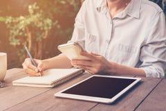 关闭手妇女文字笔记本和藏品电话在咖啡 免版税库存图片