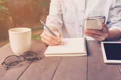 关闭手妇女文字笔记本和藏品电话在咖啡 库存照片