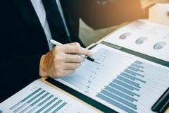 关闭手投资者用完计算器计算公司的收入投资在未来赢利的库存 免版税库存照片