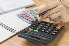 关闭手按在计算器的妇女按钮有预算、费用和费用名单的在小笔记薄,金钱和 库存图片