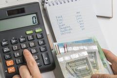 关闭手按在计算器的妇女按钮有预算、费用和费用名单的在小笔记薄,金钱 库存图片